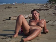 Sweaty wife posing nude on the beach, spreading round legs with a tight shaven crack..